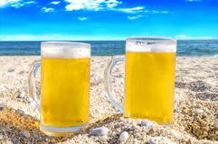 Photo of two cold beer bottle in the sand on the beach Royalty Free Stock Photos