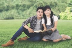 Two students with a book in the park Stock Photography