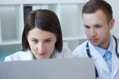 Two young doctors together discussing new way of treatment while having a meeting at office. Doctors using desktop. Photo of two doctors together discussing new Royalty Free Stock Images