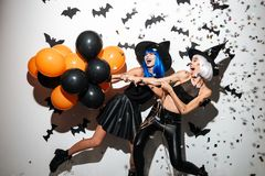 Emotional young women in halloween costumes Stock Photography