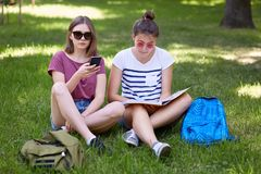 Photo of two female teenagers sit on green grass outdoor, read book and uses mobile phone for surfing social networks, wear sungla royalty free stock photography