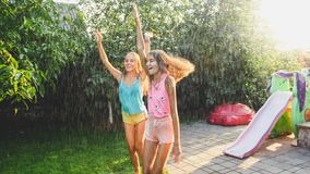 Photo of two happy laughing sisters in wet clothes dancing under water droplets from garden hose at garden. Family. Image of two happy laughing sisters in wet royalty free stock images