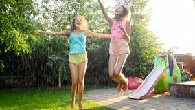 Photo of two happy laughing sisters in wet clothes dancing under water droplets from garden hose at garden. Family. Image of two happy laughing sisters in wet stock photo