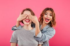 Two ladies friends covering eyes with hands. stock images