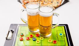 Photo of two mugs of frothy beer, table football. Pizza on white table royalty free stock images