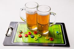 Photo of two mugs of frothy beer, table football. On white table stock photo