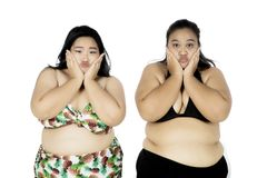 Two fat women look bored on studio. Photo of two women wearing swimwear and looking at the camera with bored expression, isolated on white background Royalty Free Stock Photo