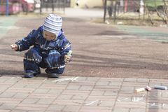 A 2 -year-old boy painting with chalk outdoors. Photo of a two years old boy, wearing dark white-blue-black coveralls and a hat, painting with colour chalk Stock Images