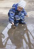 A 2 -year-old boy playing with a leaf in a puddle. Photo of a two years old boy, wearing waterproof  childrens clothing, playing in a puddle with a leaf in Stock Photos