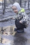 A 2 -year-old boy playing with a wooden stick in a puddle. Photo of a two years old boy, wearing waterproof  childrens clothing, playing in a puddle with a Royalty Free Stock Photo