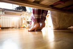 Photo from under the bed on barefoot woman in pajamas. At morning royalty free stock image