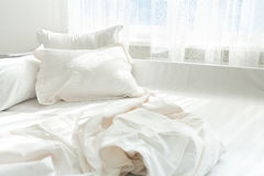 Photo of untidy bed against window Royalty Free Stock Image