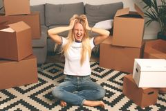 Photo of upset woman sitting on floor among cardboard boxes royalty free stock photo