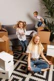 Photo of upset woman sitting on floor among cardboard boxes and boy and girl stock photography
