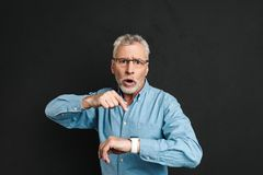 Photo of uptight gentleman 60s with grey hair wearing eyeglasses. Pointing finger at his wrist watch with shock isolated over black background Stock Images