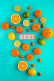 Photo of various citrus fruits and nuts on plain cyan background royalty free stock image