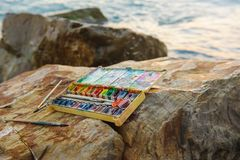 Photo used water-color paint-box, paint brushon ,brushes on stones near the sea shore. Stock Photos