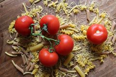 Top view of the Italian pasta fusilli with fresh vegetables, tomatoes stock photos