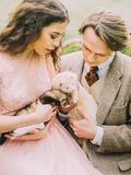 The photo of the vintage dressed just married holding the brown and white ferret and enjoying the down time in the green Stock Photos