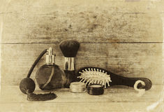 Photo of vintage perfume bottle next to old wooden hairbrush on wooden table. black and white old style photo Stock Photos