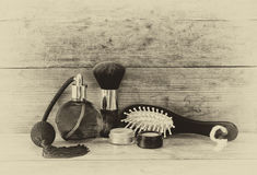 Photo of vintage perfume bottle next to old wooden hairbrush on wooden table. black and white old style photo Royalty Free Stock Photos