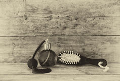 Photo of vintage perfume bottle next to old wooden hairbrush on wooden table. black and white old style photo Stock Photo