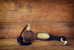 Photo of vintage perfume bottle next to old wooden hairbrush on wooden table. retro filtered image Stock Photos