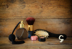 Photo of vintage perfume bottle next to old wooden hairbrush on wooden table. retro filtered image Royalty Free Stock Photos