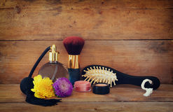 Photo of vintage perfume bottle next to old wooden hairbrush on wooden table. retro filtered image Royalty Free Stock Image