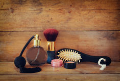Photo of vintage perfume bottle next to old wooden hairbrush on wooden table. retro filtered image Stock Photo