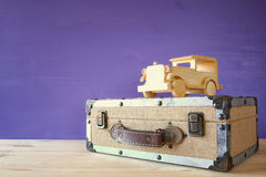 Photo of vintage toy car and old suitcase. On wooden table royalty free stock images