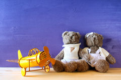 Photo of vintage toy plane and couple of cute teddy bears. On wooden table. Filtered and toned image stock images