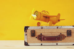 Photo of vintage yellow toy plane and old suitcase Stock Photo