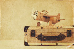 Photo of vintage yellow toy plane and old suitcase Royalty Free Stock Images