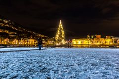 Winter City Scene with A Lone Man Standng on Snow and Looking at Glowing Christmas Tree royalty free stock photo