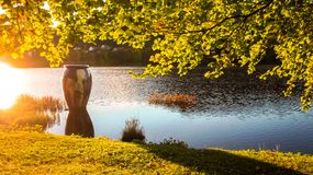 Autumn Landscape with Colorful Tree Branches, Sun Flare and A Big Vase by A Lake at Sunset royalty free stock photography
