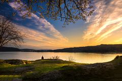 A Lone Woman Sits by Fjord at Sunset in Bergen stock photography