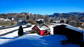 Winter Landscape with Snowy Houses and Mountains with A Red House in The Center and Clear Blue Sky in A Sunny Day stock images