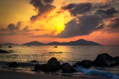 Nature Seascape with Tranquil Beach, Boulders, Islands, Dark Clouds and Hidden Sun at Sunrise. This photo was taken at Binh Lap, a peninsula located in Cam Ranh stock image