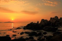 Nature Seascape with Boulders, The Sun and Waves at Gorgeous Orange Sunrise royalty free stock photography