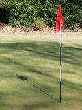 Golf green with red flag casting shadow stock photos