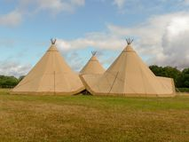 Three large tepees set up for a wedding event on farmland stock image