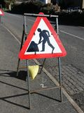 Triangular road works sign on metal frame by roadside royalty free stock photos