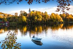 Autumn Landscape with A Lone Boat, Colorful Trees and Houses Reflected in Lake stock photography