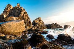Nature Seascape with Rough Boulders, Pristine Beach and Surging Waves in Morning Sunshine royalty free stock photos