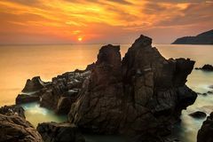Nature Seascape with Exotic Boulders, Silky Water at Gorgeous Orange Sunrise royalty free stock photography