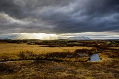 Godrays Sunset View Iceland towards mountains with grass water a Royalty Free Stock Photos