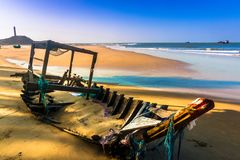 Seascape with A Broken Old Fishing Boat on Sandy Beach in Morning Sunshine stock images