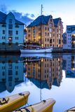 City Scene with Traditional Houses and Boats Reflected in A Calm Canal at Night in Alesund. Image of Alesund after midnight in Summer. Alesund is a port town on royalty free stock photo