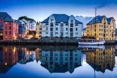 City Scene with Traditional Houses and Boat Reflected in A Calm Canal at Night in Alesund. Image of Alesund after midnight in Summer. Alesund is a port town on stock photography